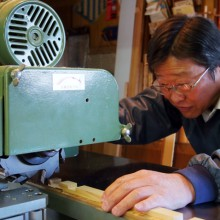 最新の機械を使って組子細工の材料を裁断する高田さん