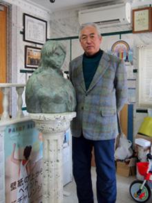 本物以上を目指した石柱と銅像と写る木暮さん